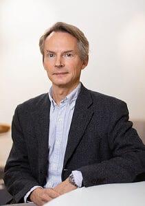 Hans Pohl, programchef vid STINT sitter vid ett bord