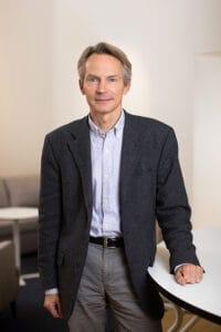 Pressbild på Hans Pohl, programchef vid STINT står vid ett bord.