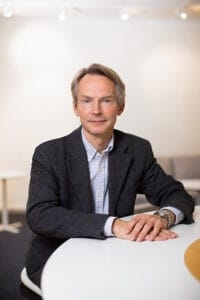 Pressbild: Hans Pohl, programchef vid STINT sitter vid ett bord.